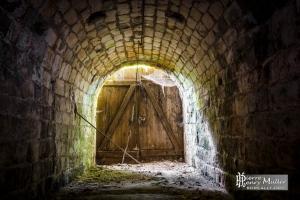 Sortie du tunnel fermée par une porte en bois laissant passer la lumière. Photo @CC Pierre-Henry Muller